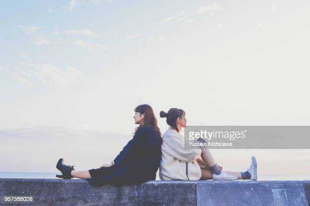 two young women sitting back to back - yusuke nishizawa fotografías e imágenes de stock