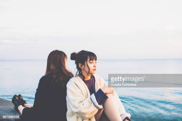 two young women sitting back to back - yusuke nishizawa photos et images de collection