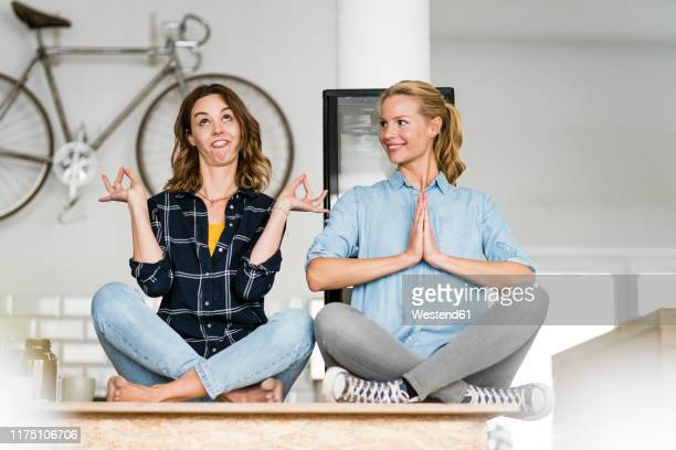 two young women sitting cross-legged on the counter of their coffee shop, one meditating , other pulling funny faces - gegensatz stock-fotos und bilder
