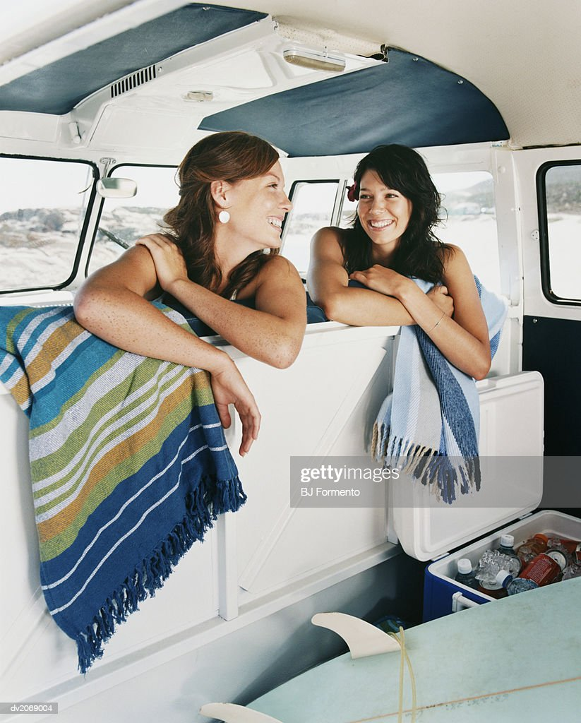 Two Young Women Sitting in a Camping Van Smiling : Stock Photo
