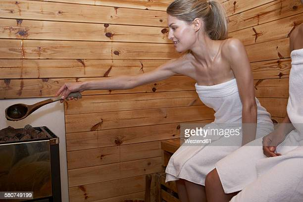 Two young women sitting in a sauna