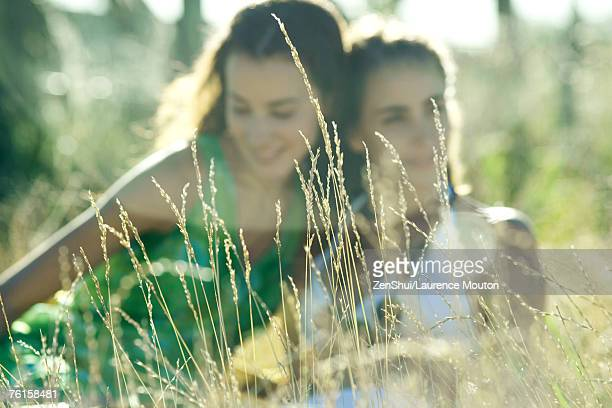 Two young women sitting in field, focus on weeds in foreground