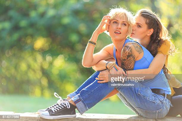 Two young women sitting in park and resting