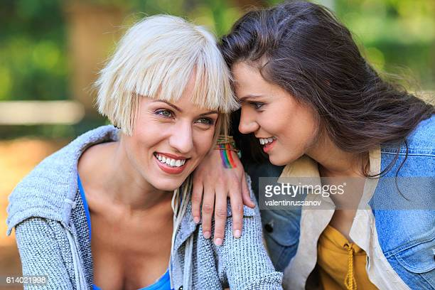 two young women sitting in park and talking - transexual stock photos and pictures