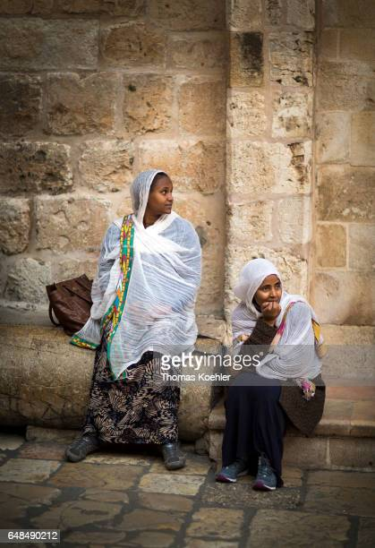 Two young women sitting on a square in front of the Church of the Holy Sepulchre historic city center of Jerusalem on February 08 2017 in Jerusalem...