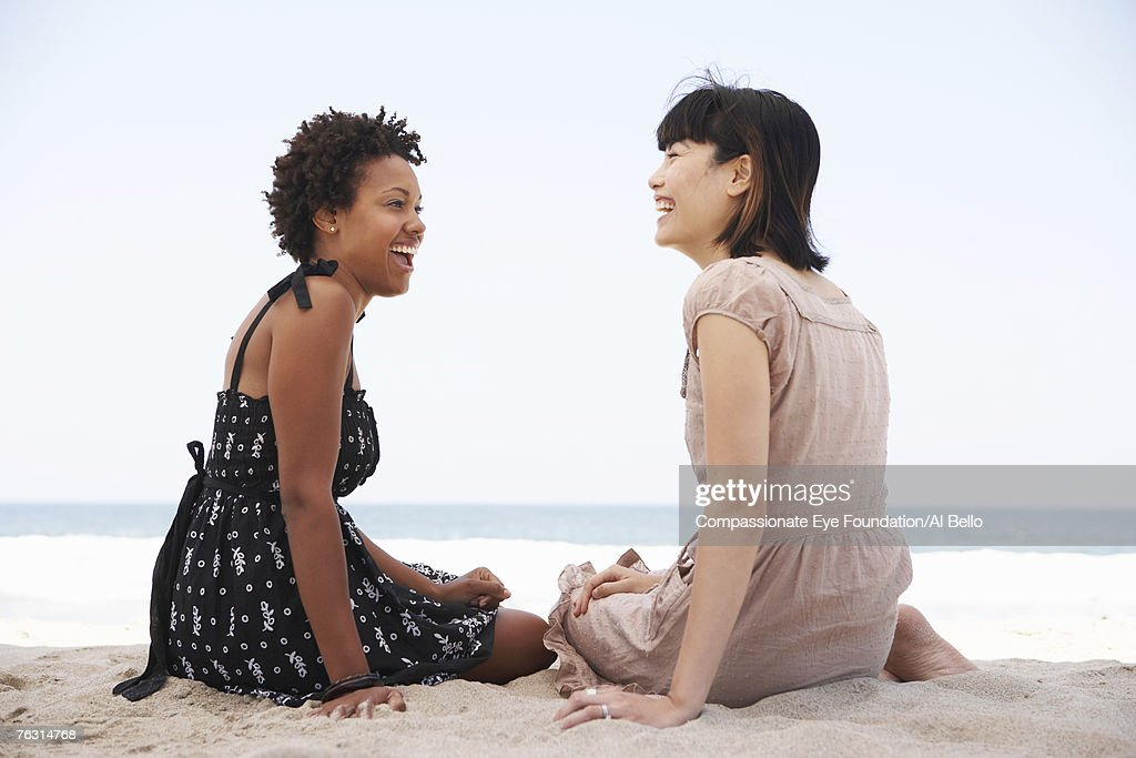 Two young women sitting on beach laughing : Foto de stock