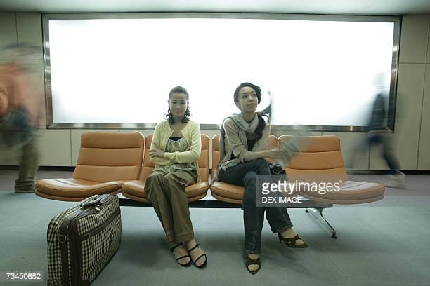 Two young women sitting on chairs and waiting