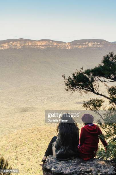 two young women sitting on cliff - blue mountains national park stock pictures, royalty-free photos & images