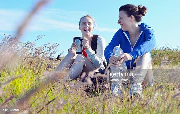 Two young women sitting on grass, drinking and talking