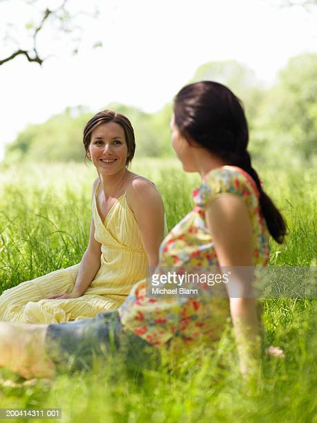 Two young women sitting on grass in park (focus on woman smiling)