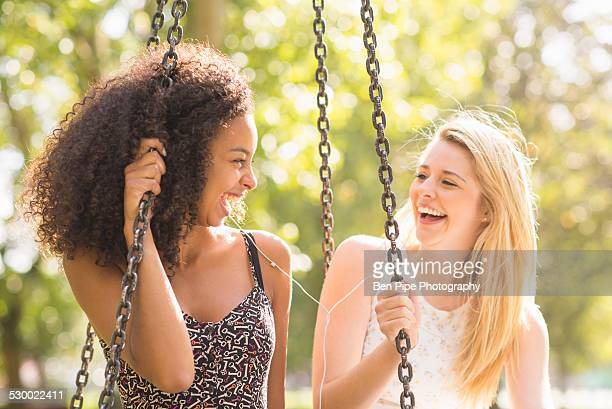 Two young women sitting on park swing laughing