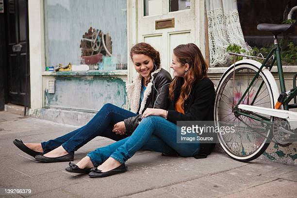 Two young women sitting on pavement outside cafe