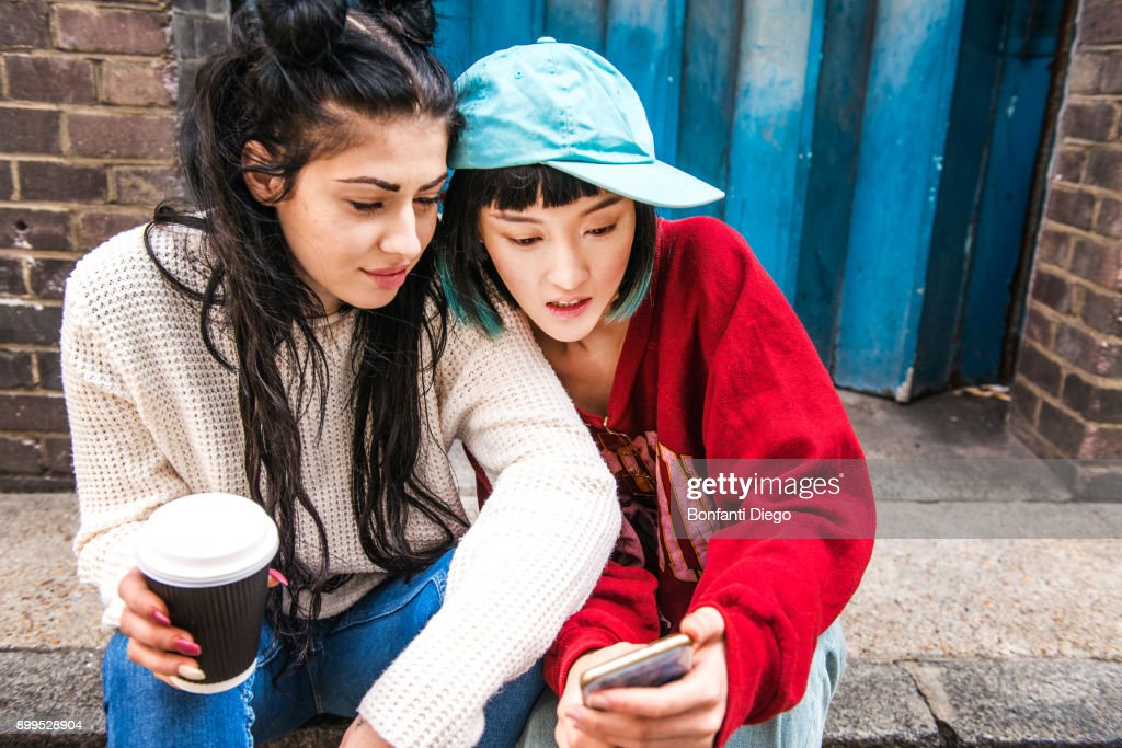 Two young women sitting on sidewalk looking at smartphone : Stock Photo