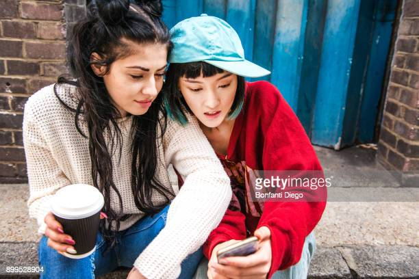 two young women sitting on sidewalk looking at smartphone - generation z stock pictures, royalty-free photos & images