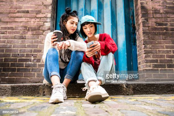Two young women sitting on sidewalk looking at smartphone
