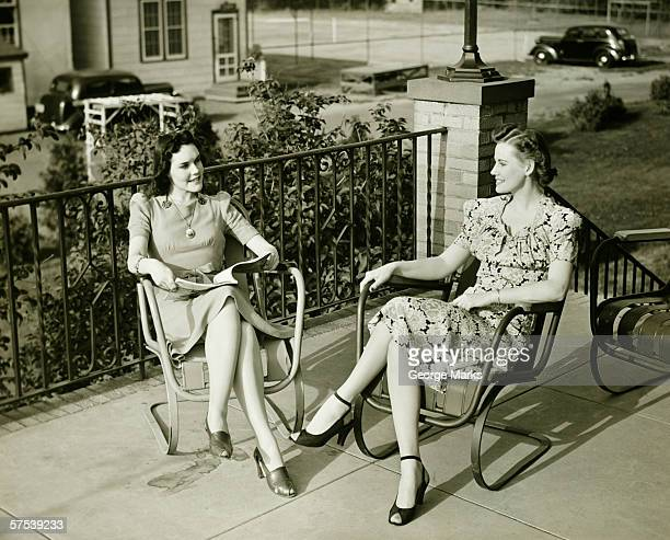 Two young women sitting on terrace, talking, (B&W)
