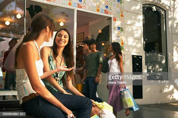 Two young women sitting outdoors by shop, smiling