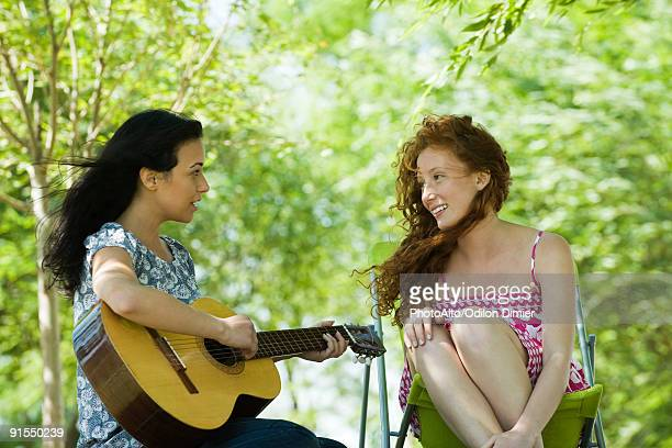 Two young women sitting outdoors, one playing acoustic guitar