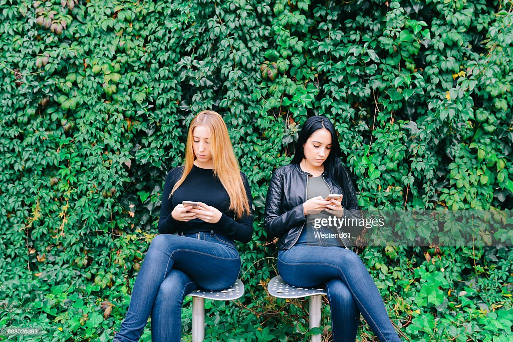 Two young women sitting side by side using their cell phones : Stock Photo