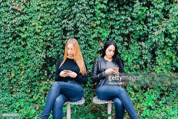 Two young women sitting side by side using their cell phones