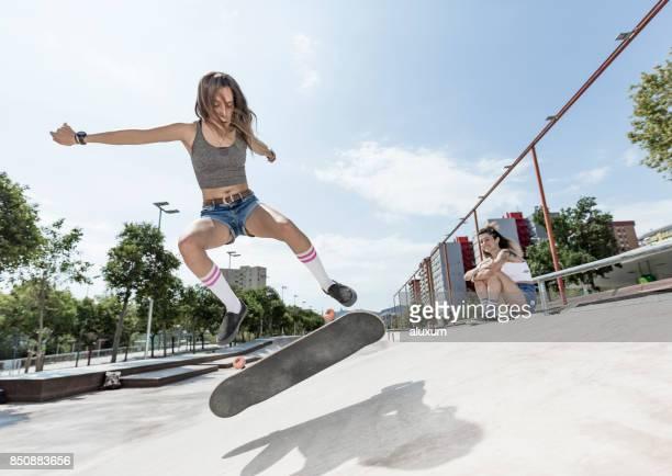 dos mujeres jóvenes skate y saltar - truco fotografías e imágenes de stock