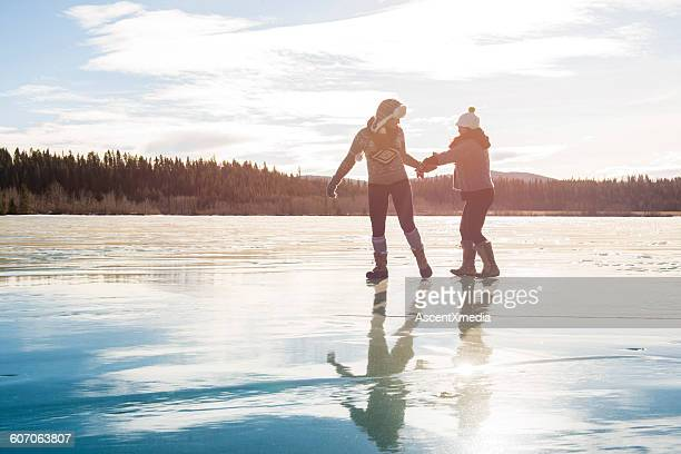 Two young women slide along ice, frozen lake