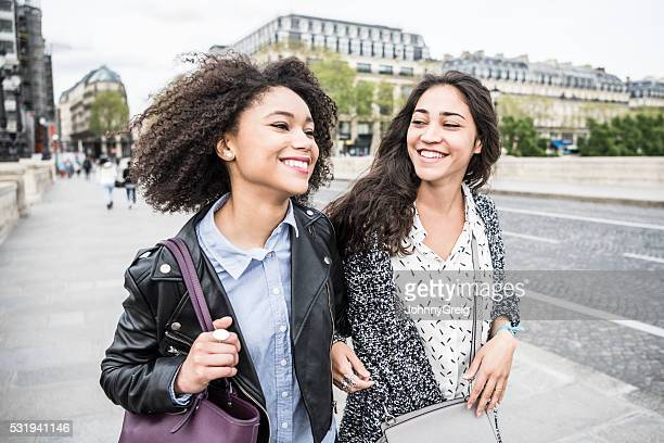 Two young women smiling and talking in Paris