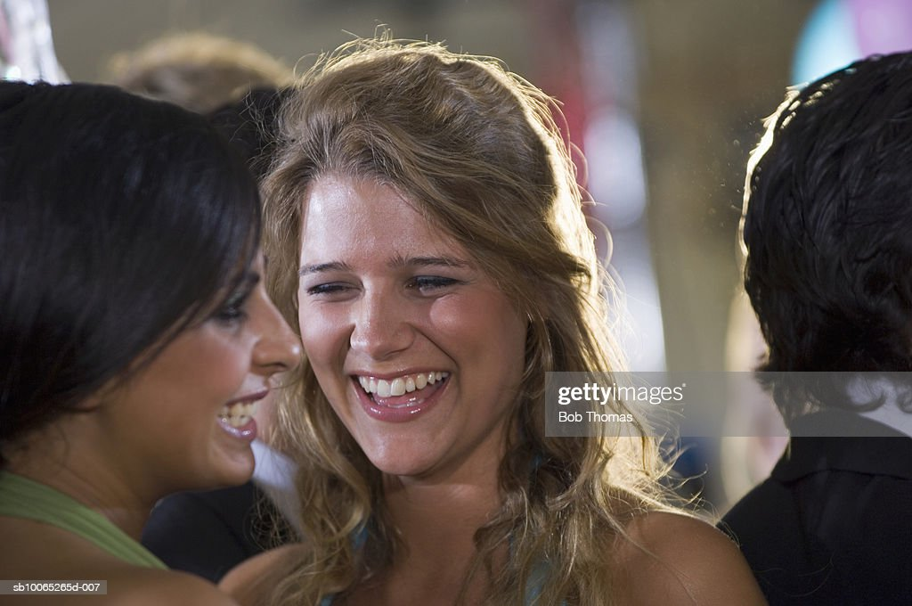 Two young women, smiling, close-up (focus on foreground) : Foto stock