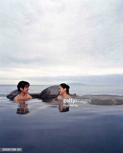 Two young women soaking in hot spring, sea in background