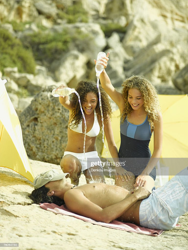 two young women squirting water with water bottles on a young man