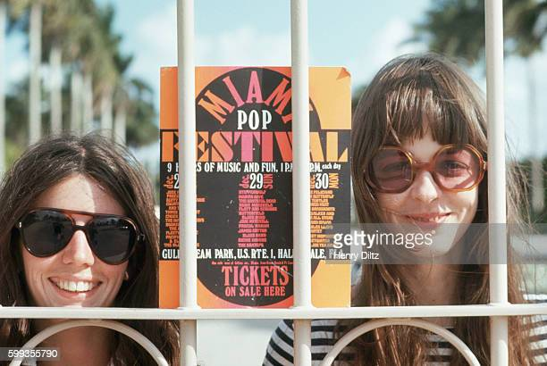 Two young women stand outside the gates of the Hallendale Racetrack during the Miami Pop Festival