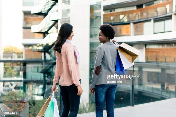 two young women standing and carrying shopping bags - afro caribbean ethnicity stock pictures, royalty-free photos & images