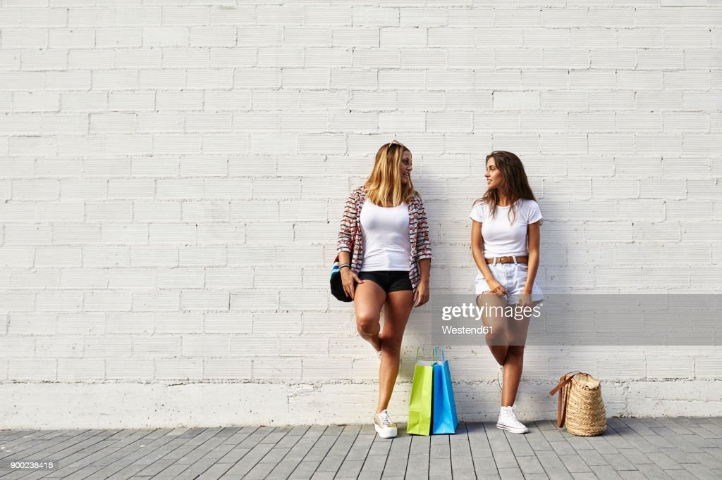 Two young women standing at white wall with bags : Stock Photo