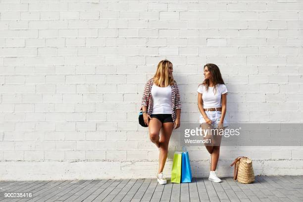 Two young women standing at white wall with bags