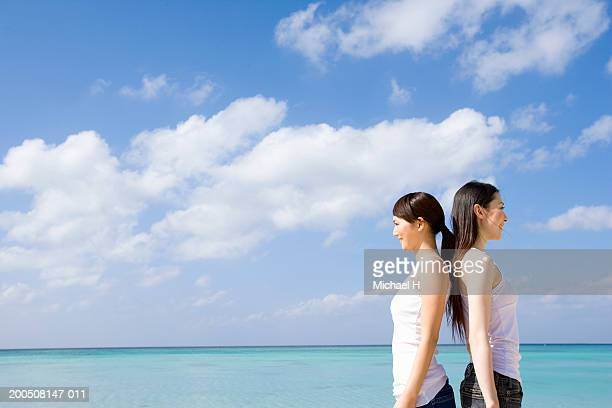 two young women standing back to back on beach, side view - 背中合わせ ストックフォトと画像