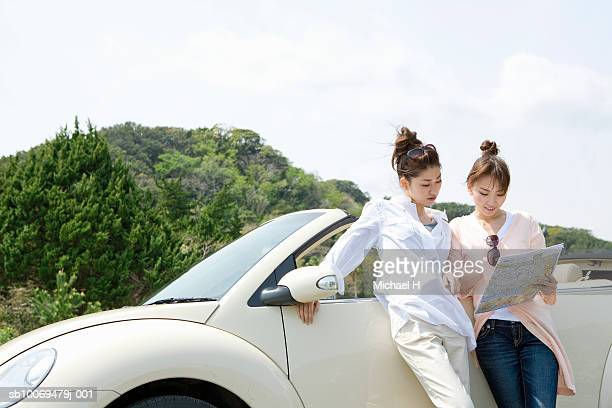 Two young women standing by car looking at map