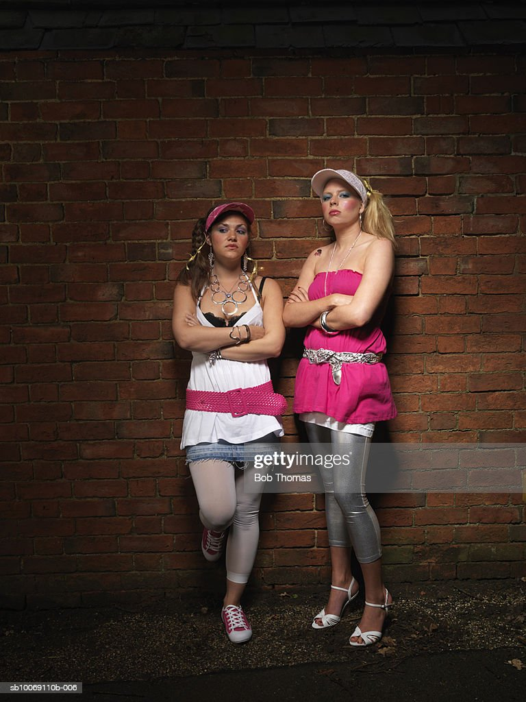Two young women standing in front of brick wall : Stockfoto