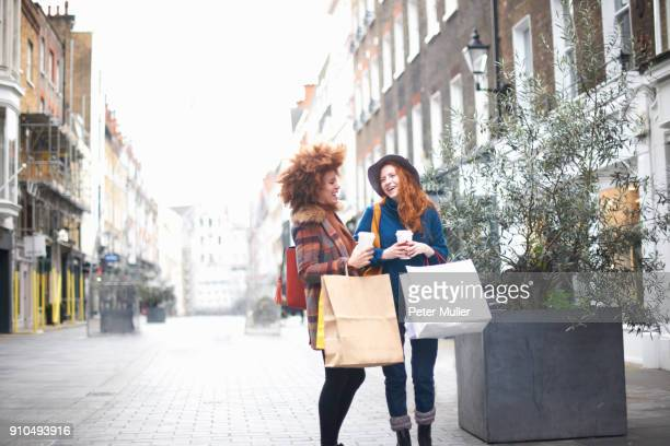 two young women standing in street, holding shopping bags and coffee cup - western europe stock pictures, royalty-free photos & images