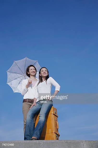 Two young women standing on breakwater