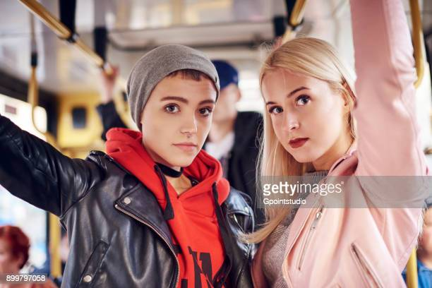 Two young women standing on city tram