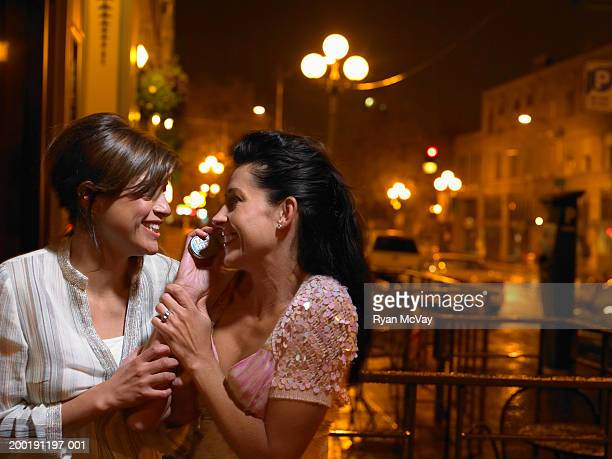Two young women standing outside talking on mobile phone, night