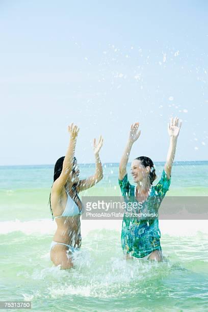 Two young women standing waist deep in sea, splashing