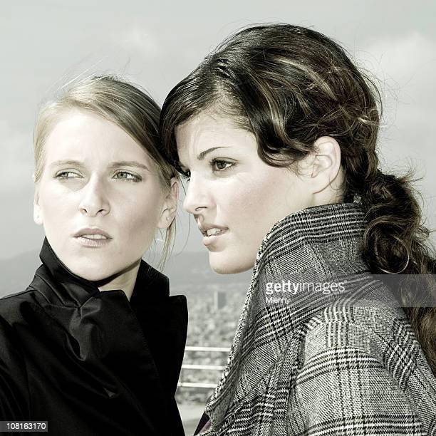 zwei junge frauen starren auf der linken seite - mlenny stock-fotos und bilder