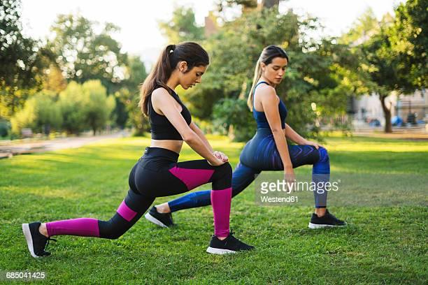 two young women stretching in park - flexionando perna - fotografias e filmes do acervo
