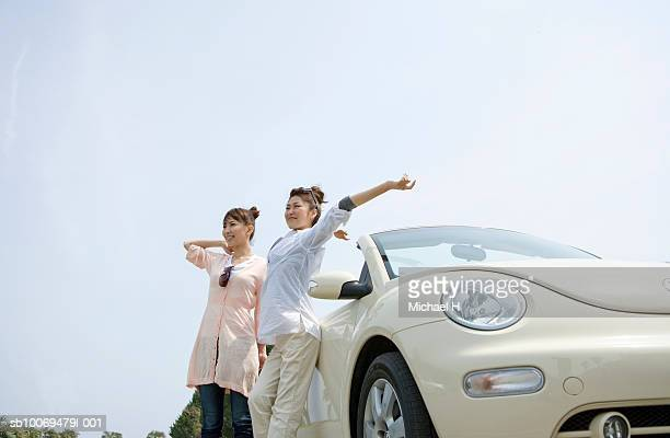 Two young women stretching, standing by stationary car, low angle view