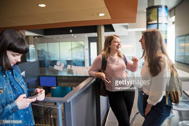 "two young women students chatting in college university lobby. - ""martine doucet"" or martinedoucet stock pictures, royalty-free photos & images"