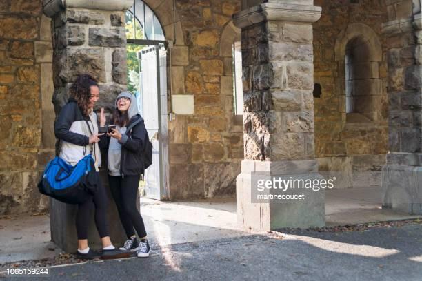 """twee jonge vrouwen studenten nemen van een pauze in de ingang van het college. - """"martine doucet"""" or martinedoucet stockfoto's en -beelden"""