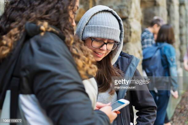 "two young women students taking a break in college entrance. - ""martine doucet"" or martinedoucet stock pictures, royalty-free photos & images"