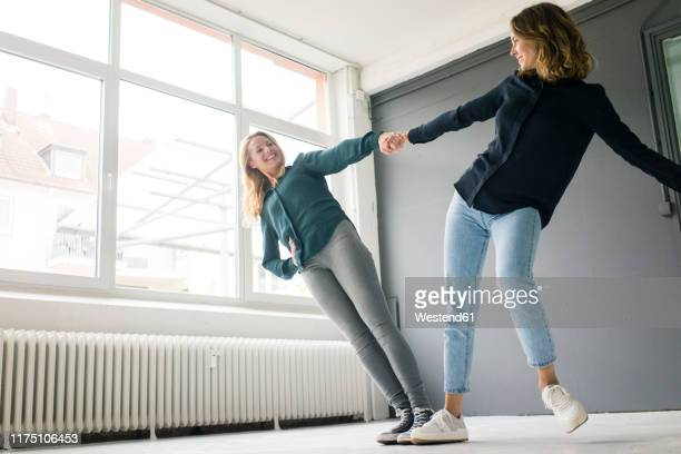 two young women supporting each other playfully - affidabilità foto e immagini stock