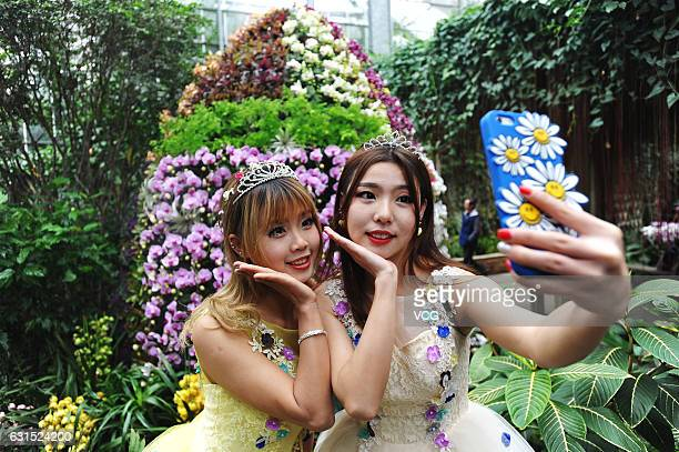 Two young women take a selfie with tropical orchids at Wuhan Botanic Garden on January 12 2017 in Wuhan Hubei Province of China Over 6500 tropical...